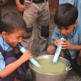 School Boys Using LifeStraw to Drink from a Water Bucket