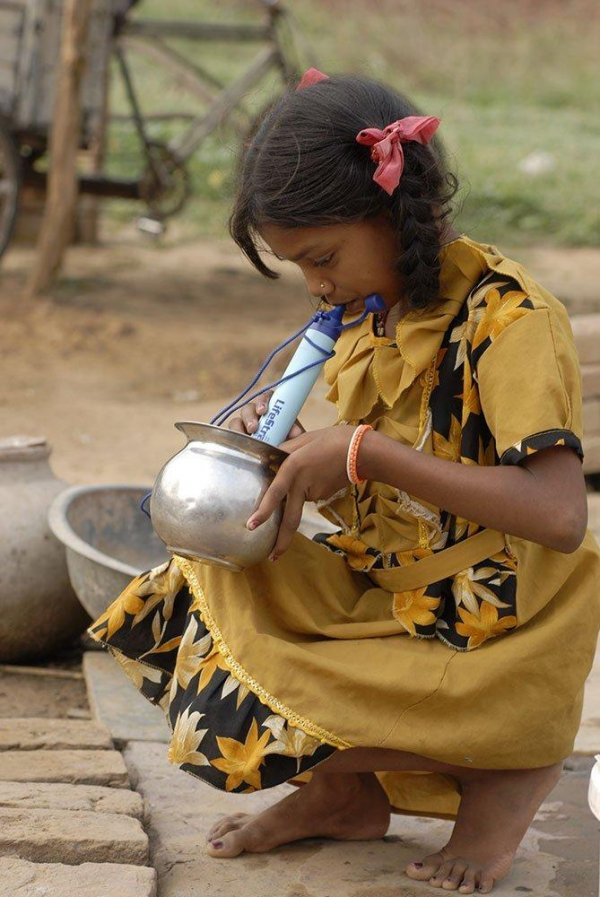Girl Using LifeStraw to Drink from a Water Bucket
